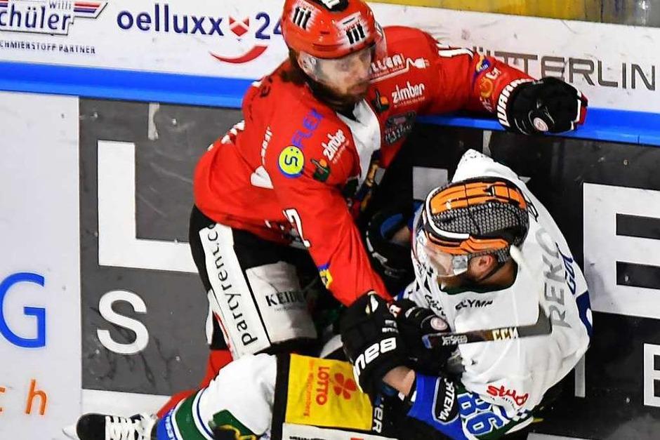 Freiburgs Andreé Hult (links, rotes Trikot) massiert Bietigheims Nicolai Goc in die Bande ein. (Foto: Achim Keller)