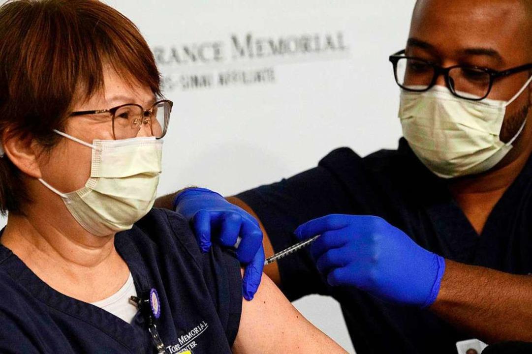 Eine Krankenschwester im kalifornische...Dezember die Impfung gegen Sars-CoV-2.  | Foto: PATRICK T. FALLON (AFP)