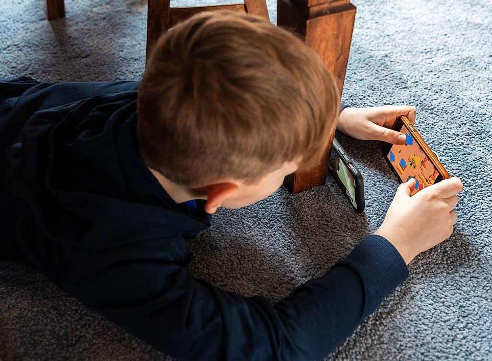 Ein Junge spielt ein Videospiel auf de... einem zweiten Handy zu seinem Freund.  | Foto: Robert Michael (dpa)