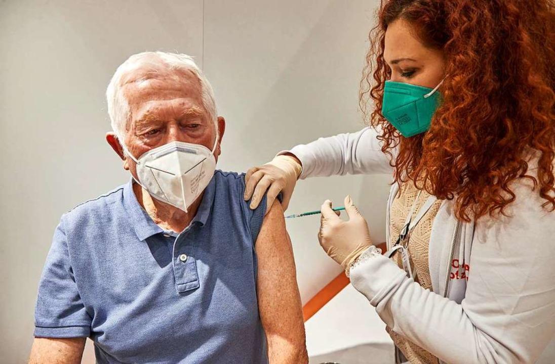 Eine medizinische Fachangestellte impft einen Senioren.  | Foto: Georg Wendt (dpa)