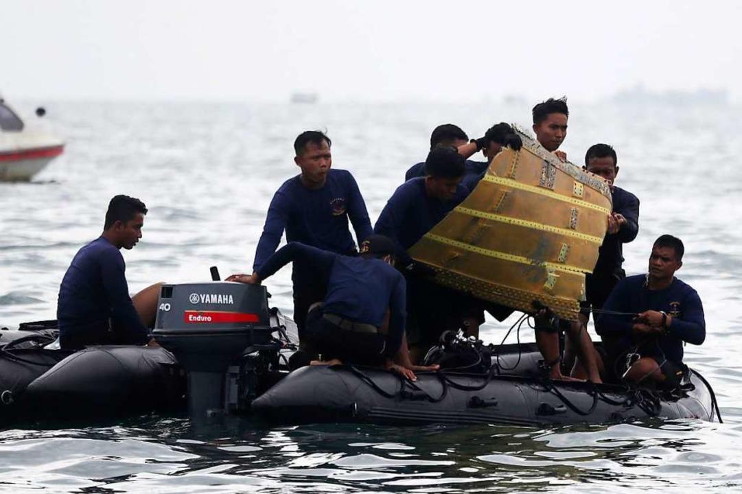 Taucher der indonesischen Marine ziehe...ugzeugteil aus dem Wasser in ein Boot.  | Foto: Achmad Ibrahim (dpa)