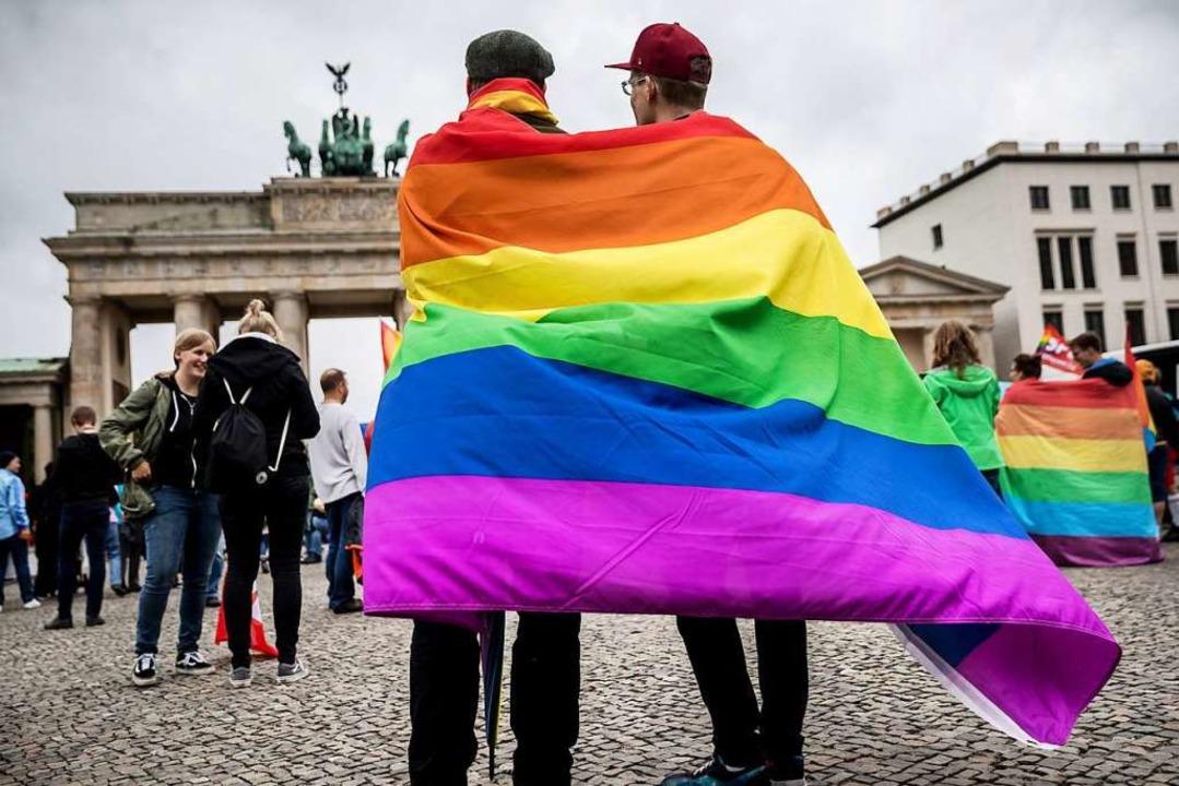 Zwei Männer haben sich eine Regenbogen...altung am Brandenburger Tor in Berlin.  | Foto: Michael Kappeler