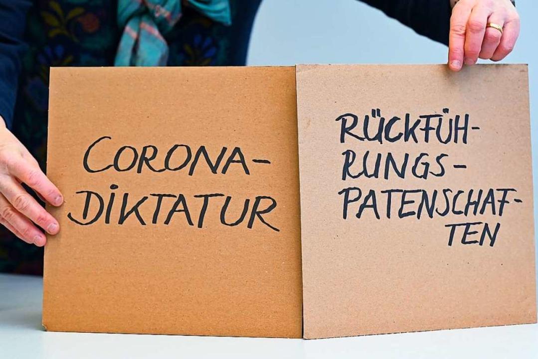 Die Unwörter auf zwei Pappschildern  | Foto: Arne Dedert (dpa)