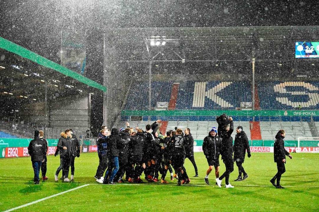 Jubel beim Kieler Team: Der Zweitligis...n der zweiten Runde aus dem DFB-Pokal.  | Foto: FABIAN BIMMER (AFP)