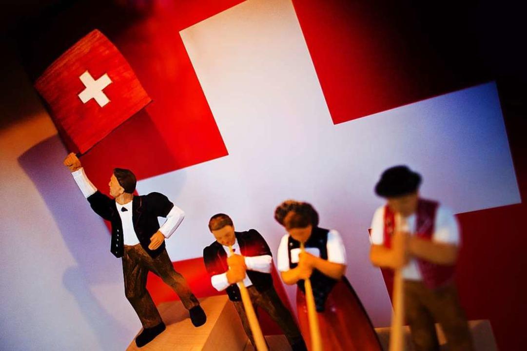 Klischees in Holz geschnitzt: Figuren mit Schweizerflagge und Alphorn  | Foto: Arno Burgi