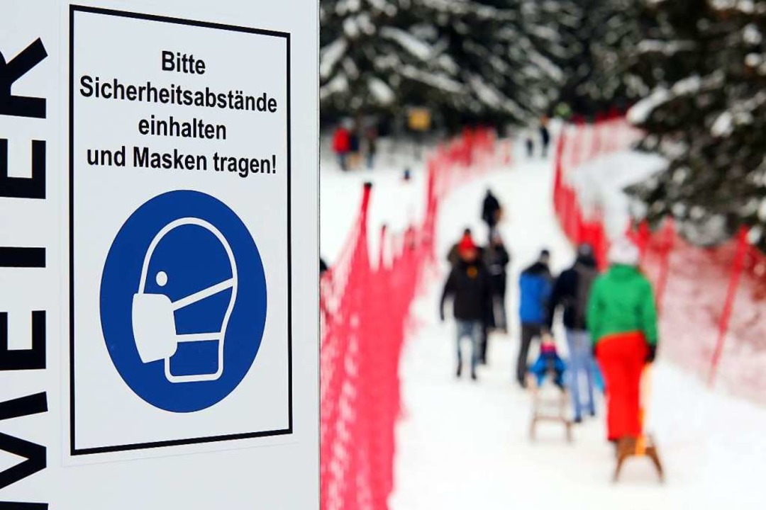 Ein Schild mit dem Hinweis zur Maskenpflicht steht am Eingang einer Skiloipe.  | Foto: Matthias Bein (dpa)