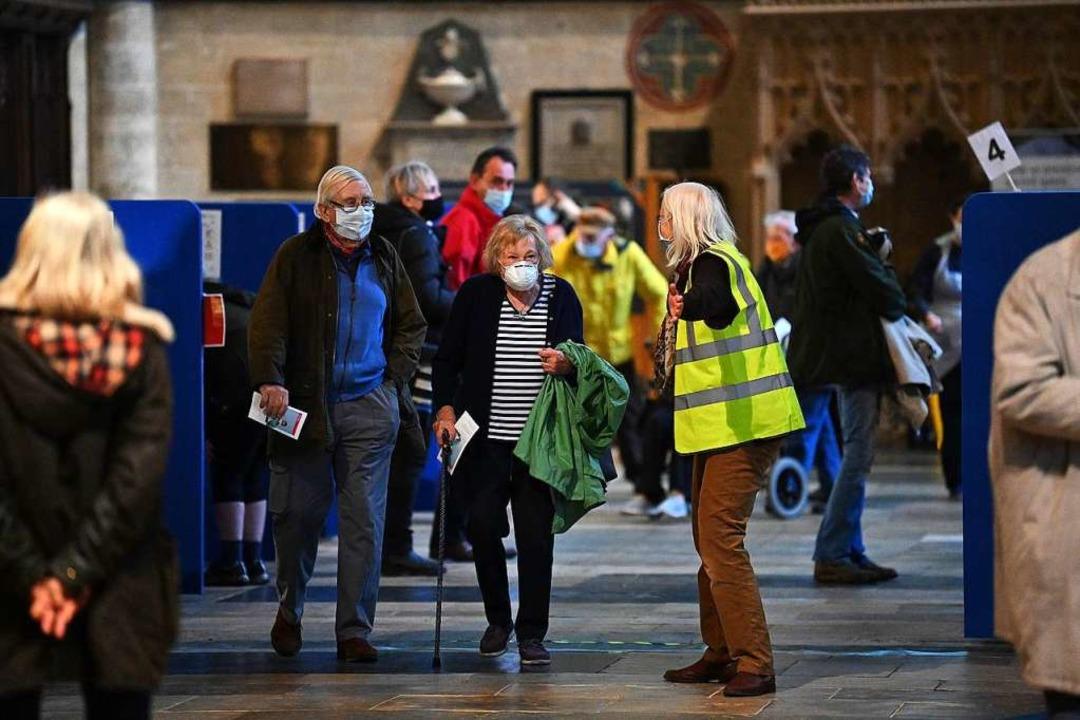 Menschen warten in der Kathedrale von Salisbury auf ihre Impfung.  | Foto: JUSTIN TALLIS (AFP)