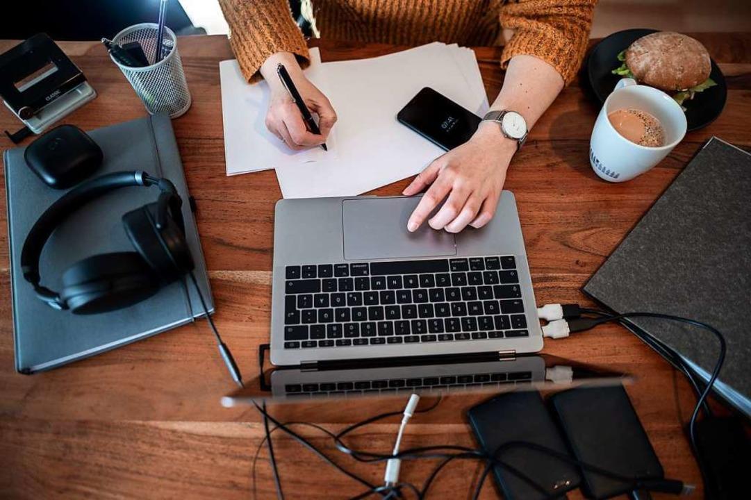 Eine Frau sitzt mit einem Laptop an einem Tisch im Homeoffice.  | Foto: Fabian Strauch (dpa)