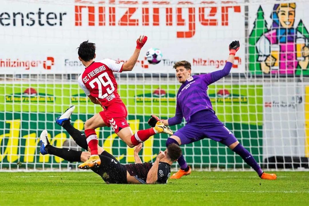 Freiburgs Woo-yeong Jeong (vorne) mach...gegen Stuttgarts Torwart Gregor Kobel.  | Foto: Tom Weller (dpa)