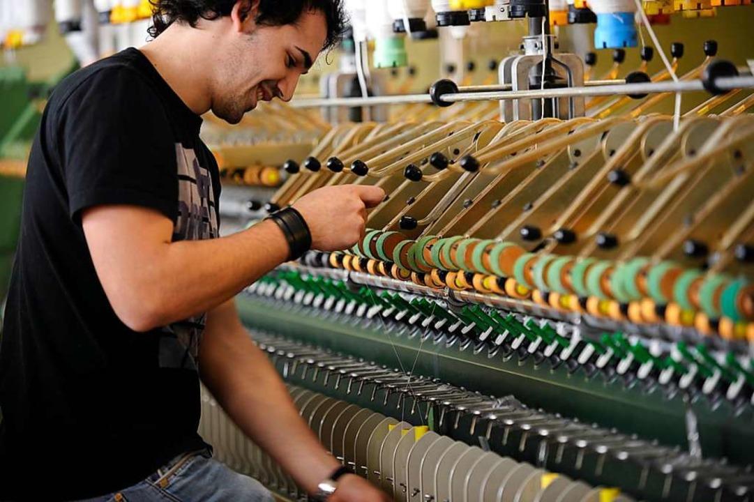 Junge Menschen lernen in der Gatex all...er ein Mitarbeiter an der Webmaschine.  | Foto: Gatex