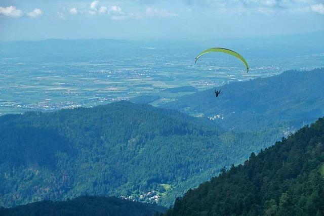 Am Gipfel des Blauen gleitet ein Paragleiter ins Tal