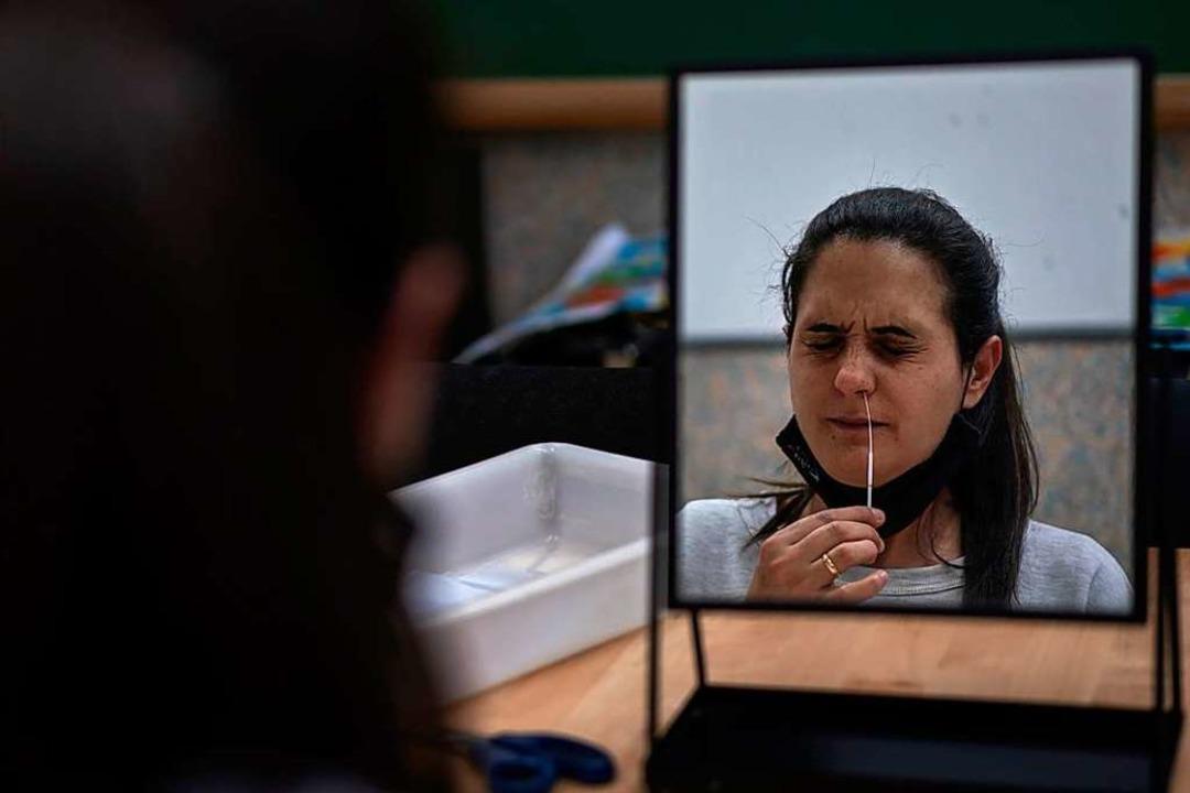 Alicia, eine Mitarbeiterin einer öffen...inen Antigentest an sich selbst durch.    Foto: Emilio Morenatti (dpa)