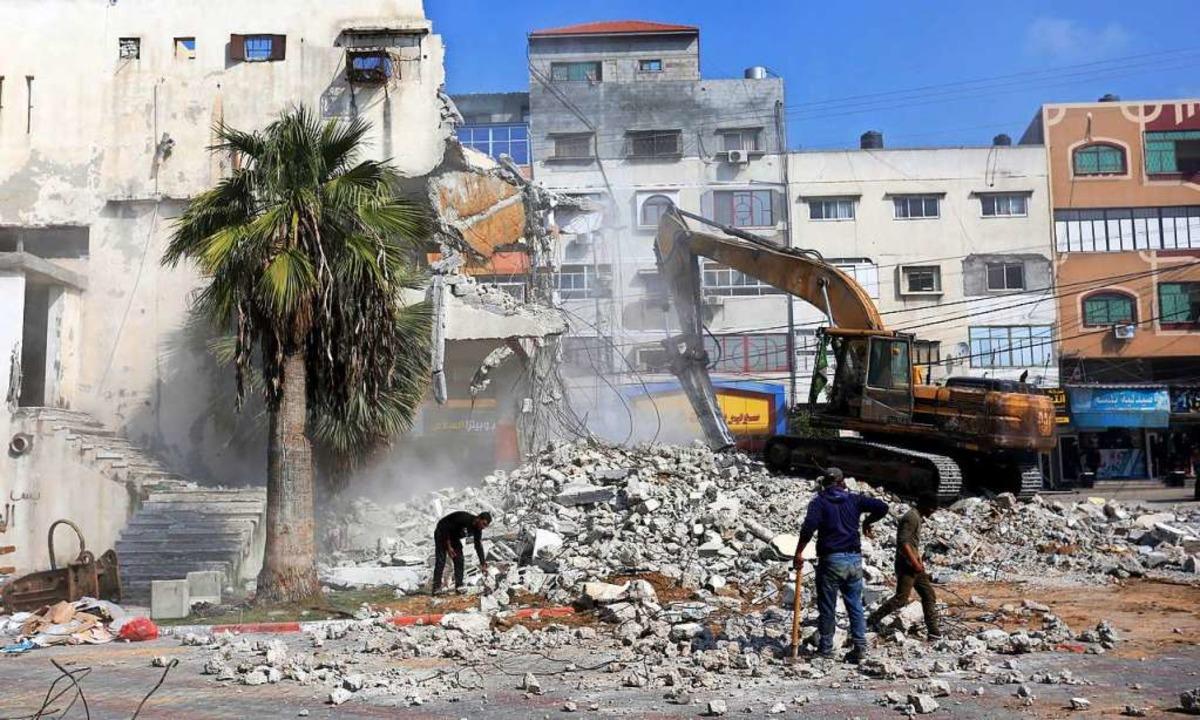 Ein im Krieg zerstörtes Gebäude im Gaza-Streifen wird abgerissen.  | Foto: Ashraf Amra (dpa)
