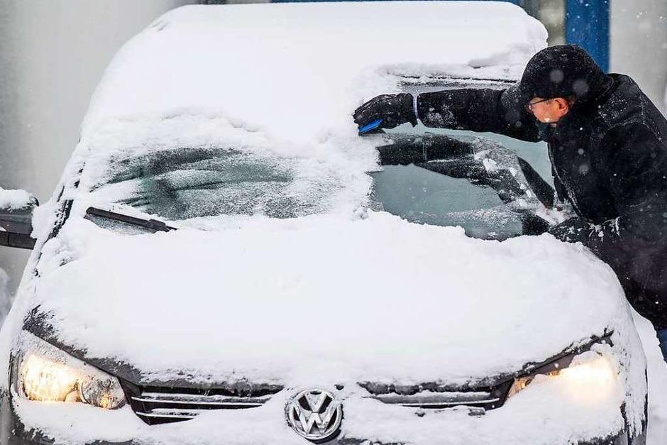 Schnee und Kälte: Ein Mann befreit seine Windschutzscheibe von Eis und Schnee in Bad Oeynhausen (Nordrhein-Westfalen). (Foto: Lino Mirgeler (dpa))