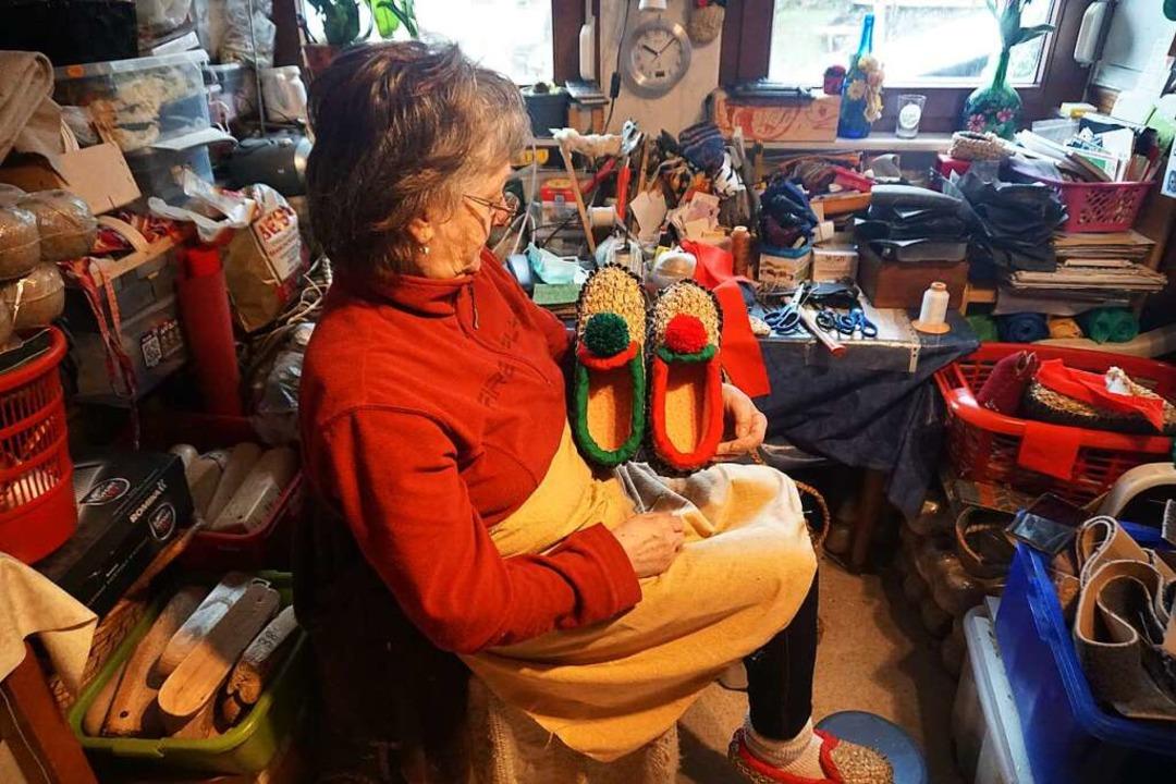 Monika Schultis in ihrer Werkstatt: . ...#8220; die rot-grünen Strohschuhe her.    Foto: Helmut Häringer