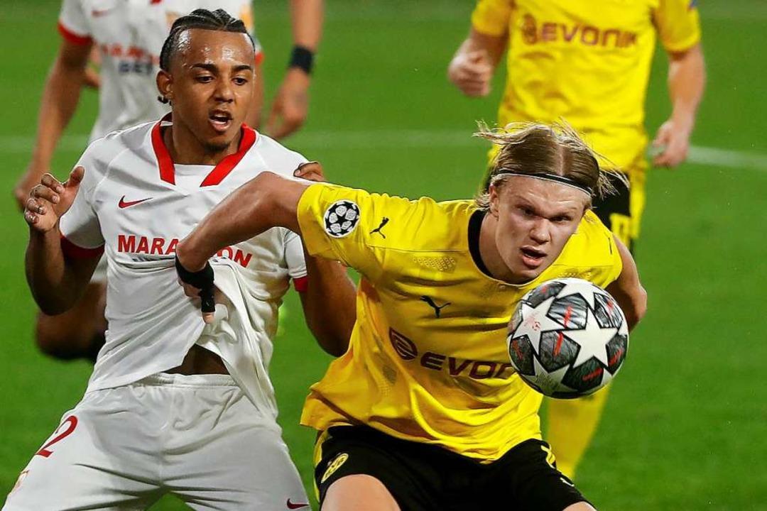 Dortmunds Erling Haaland  Sevillas Jules Kounde  kämpfen um den Ball.  | Foto: Angel Fernandez (dpa)