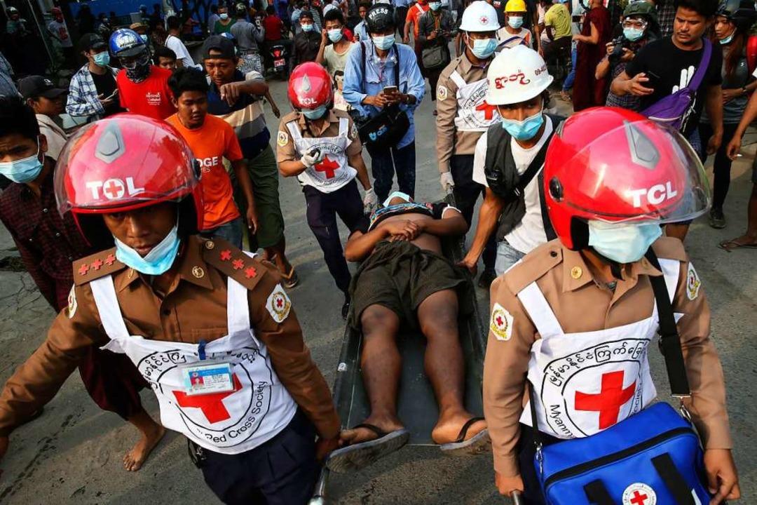 Mitarbeiter des Roten Kreuzes tragen e...leudern und Gummigeschosse einsetzten.  | Foto: -- (dpa)