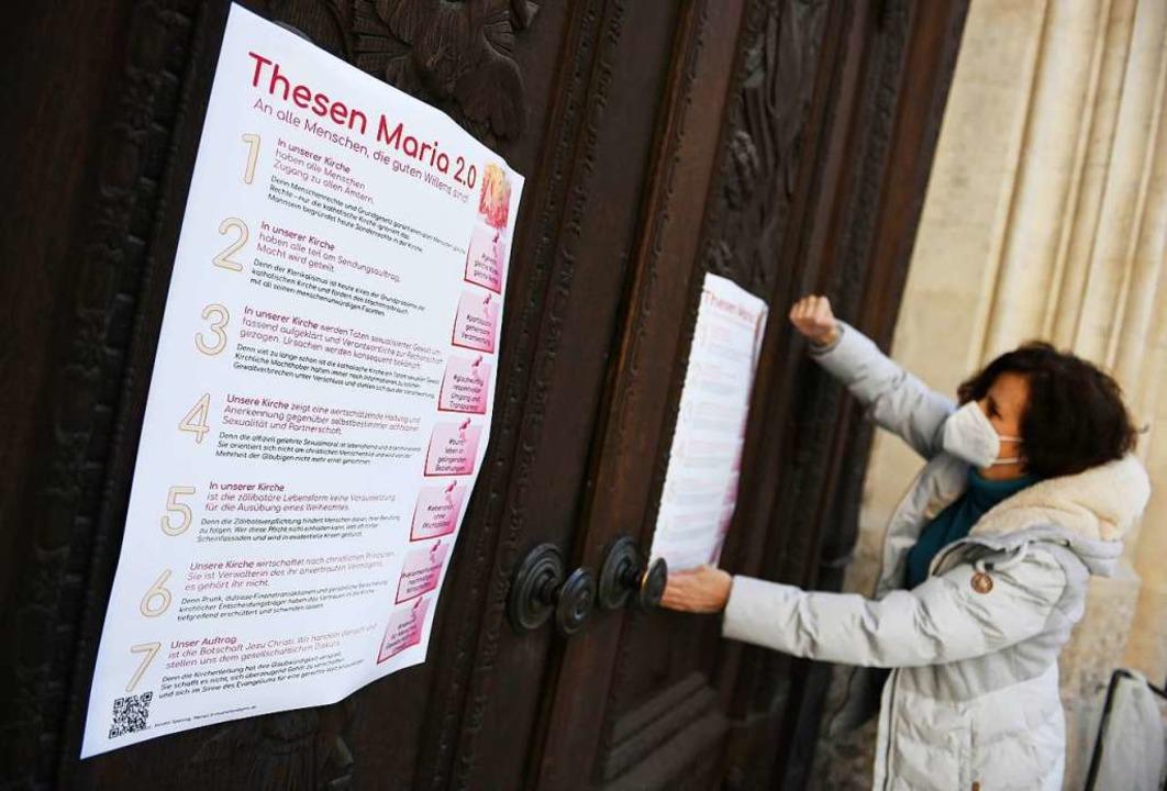 Die Aktivistin Renate Spanning hängt e...n an das Hauptportal der Frauenkirche.    Foto: Angelika Warmuth (dpa)