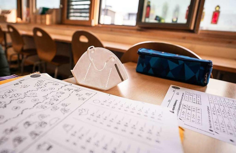 Ein FFP-2 Mund-Nasenschutz liegt in einem Klassenraum  | Foto: Frank Rumpenhorst (dpa)