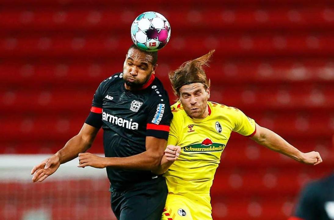 Der Freiburger Torschütze Lucas Höler ...s) im Kopfballduell gegen Jonathan Tah  | Foto: Thilo Schmuelgen (dpa)