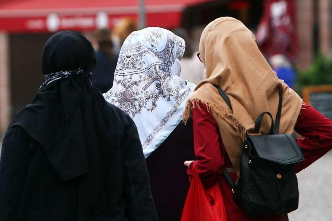 Drei Muslima mit Kopftüchern in einer Fußgängerzone  | Foto: Ralph Peters via www.imago-images.de