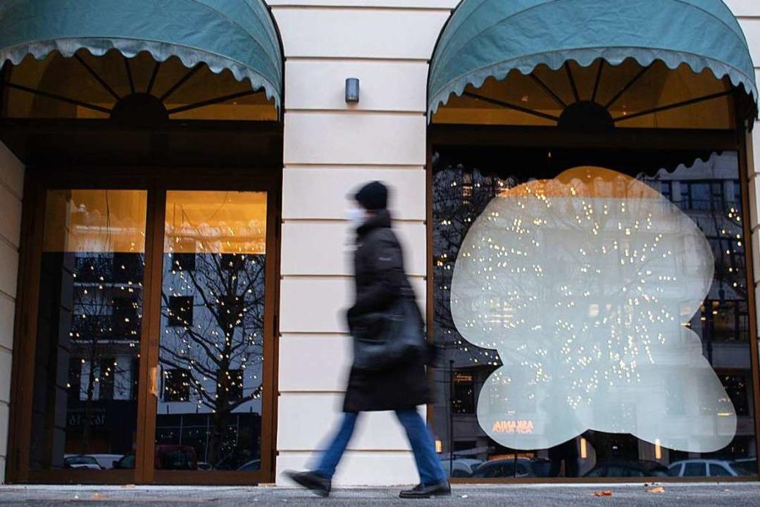 Eine Frau läuft vor leeren Schaufenstern am Kurfürstendamm entlang  | Foto: David Hutzler (dpa)