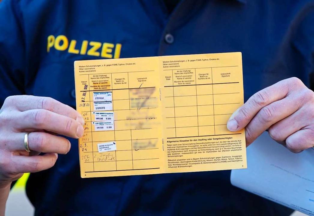 Begehrter Stempel: Ein Polizist hält d...es Probleme bei der Impfterminvergabe.  | Foto: Sven Hoppe (dpa)