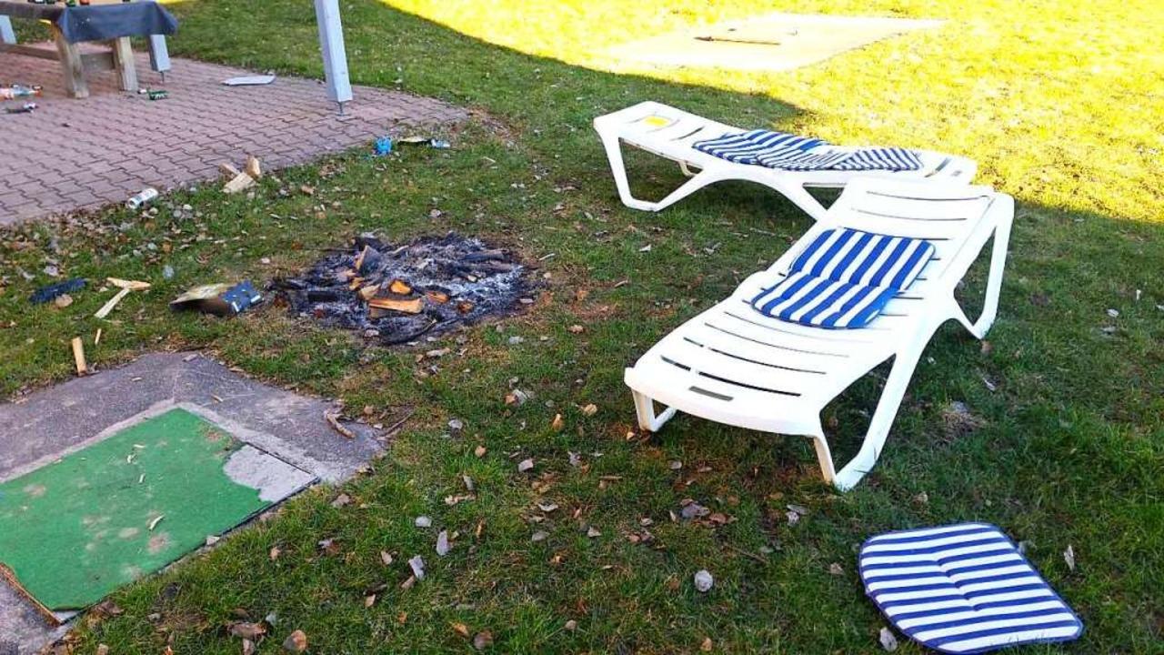 Zurückgelassen: Feuerstelle auf dem Rasen mit Sonnenliegen und Kissen.  | Foto: Eva Korinth