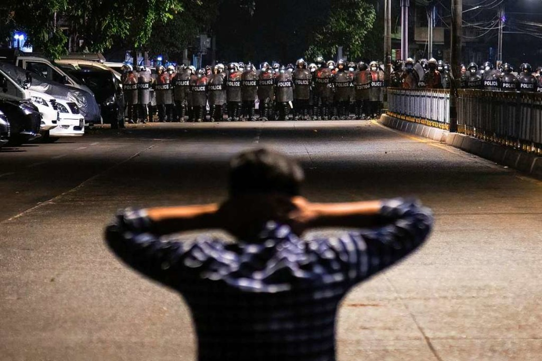 Zwei Lager stehen sich unversöhnlich g...ant  einer Reihe  Polizisten entgegen.    Foto: Theint Mon Soe (dpa)