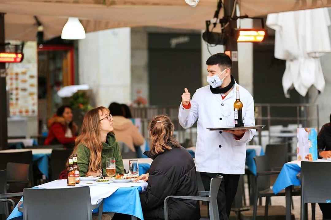 Ein Kellner bedient zwei Kundinnen auf...rasse einer Bar im Zentrum von Madrid.  | Foto: Tamara Rozas (dpa)