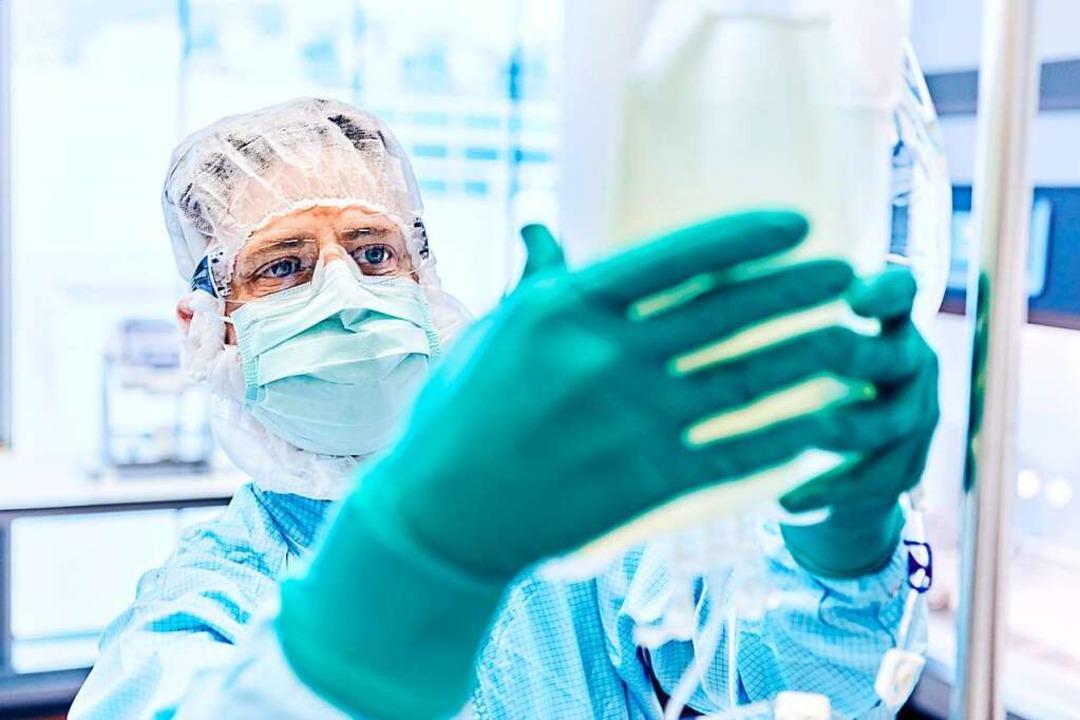 Ein Novartis-Mitarbeiter präpariert ei...hrmedium-Beutel für die Krebstherapie.  | Foto: Novartis