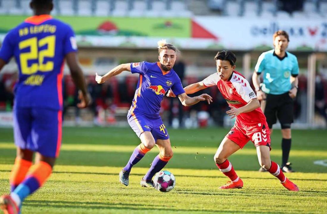 Freiburgs Mittelfeldspieler Woo-Yeong ...Mittelfeldspieler Kevin Kampl (mitte).  | Foto: Tom Weller (dpa)