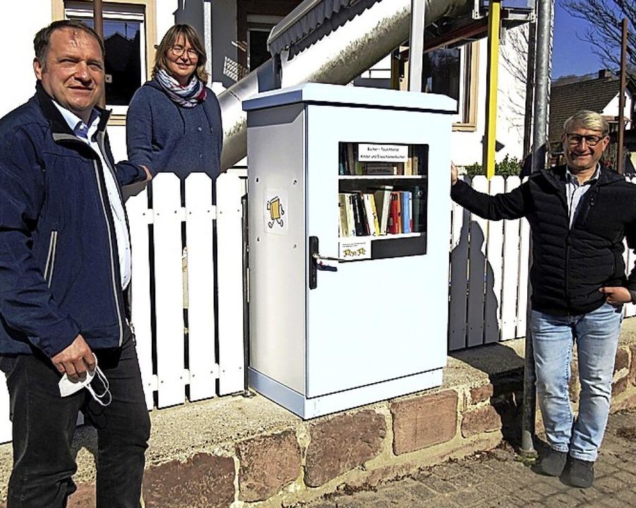 Andreas Götz, Tanja Bieber und Volker ...nks)  weihen das neue Bücherregal ein.    Foto: Reiner Merz