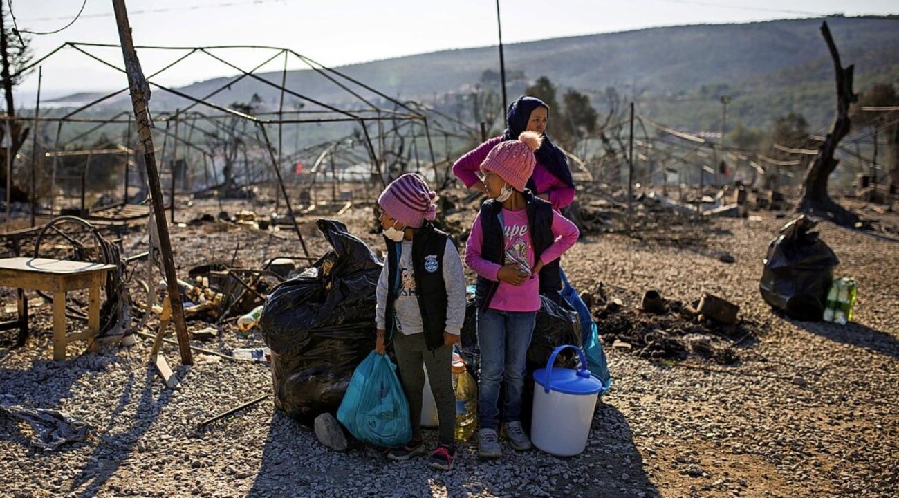 Eine Familie steht im September im ausgebrannten Flüchtlingslager Moria  | Foto: Socrates Baltagiannis (dpa)