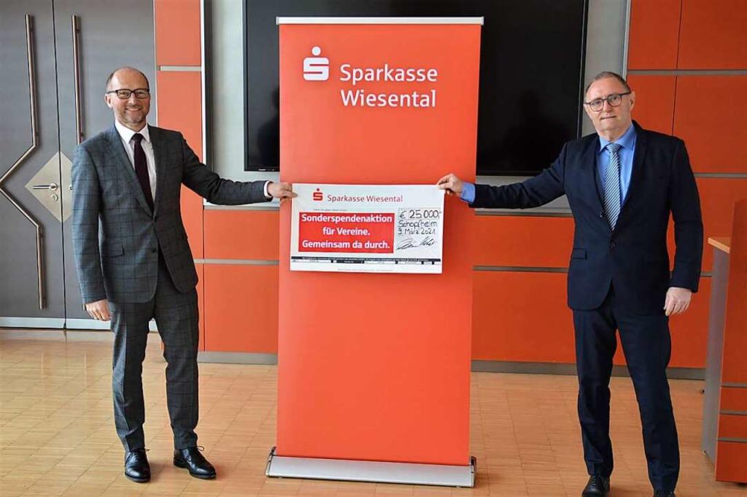 Die Sparkassenvorstände Georg Ückert (...k mit der Spendensumme von 25000 Euro.  | Foto: Edgar Steinfelder