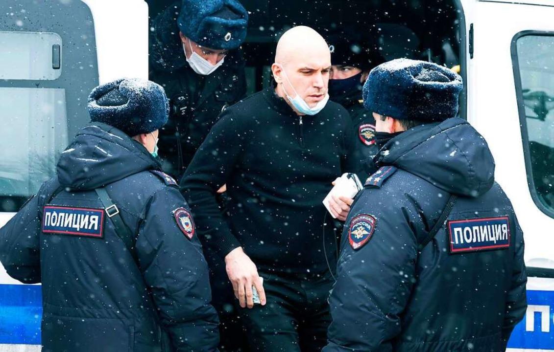 Ein Mann steht von Polizisten umgeben ...eiauto, nachdem er festgenommen wurde.    Foto: Victor Berezkin (dpa)