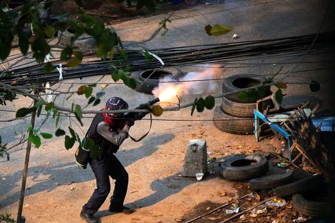 Ein Polizist schießt bei einem Anti-Pu... einem Granatwerfer auf Demonstranten.    Foto: Theint Mon Soe (dpa)
