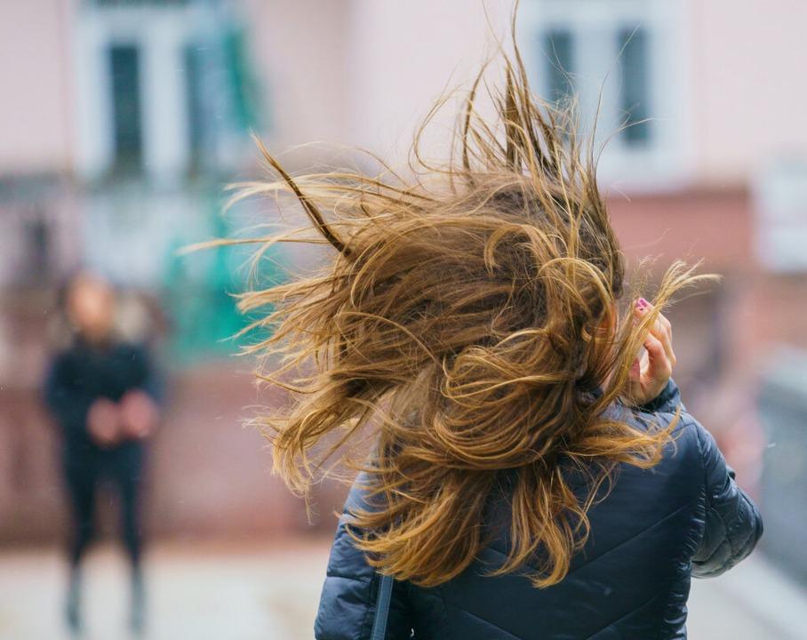 Eine Windböe wirbelt die Haare einer Frau durcheinander.    Foto: Andreas Arnold (dpa)