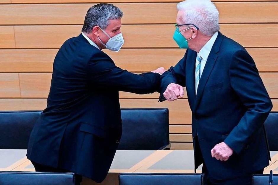 Hans-Ulrich Rülke (FDP) und Winfried Kretschmann (Grüne) begrüßen sich nachdem die ersten Hochrechnungen veröffentlicht wurden. (Foto: THOMAS KIENZLE (AFP))