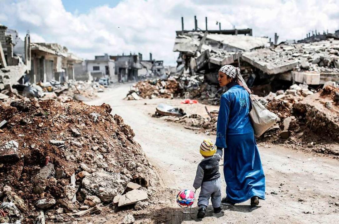 Eine Kurdin und ihre Kind laufen durch das schwer zerstörte nordsyrische Kobane.  | Foto: YASIN AKGUL (AFP)