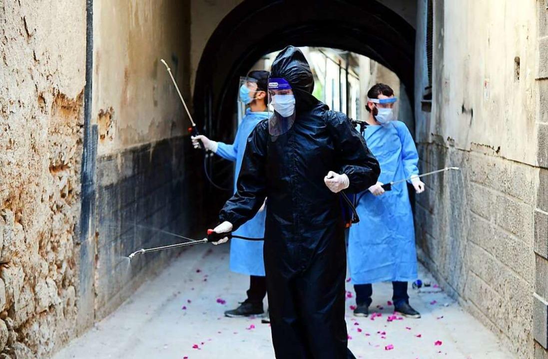 Freiwillige desinfizieren die Straßen ...virus breitet sich auch in Syrien aus.  | Foto: Ammar Safarjalani (dpa)