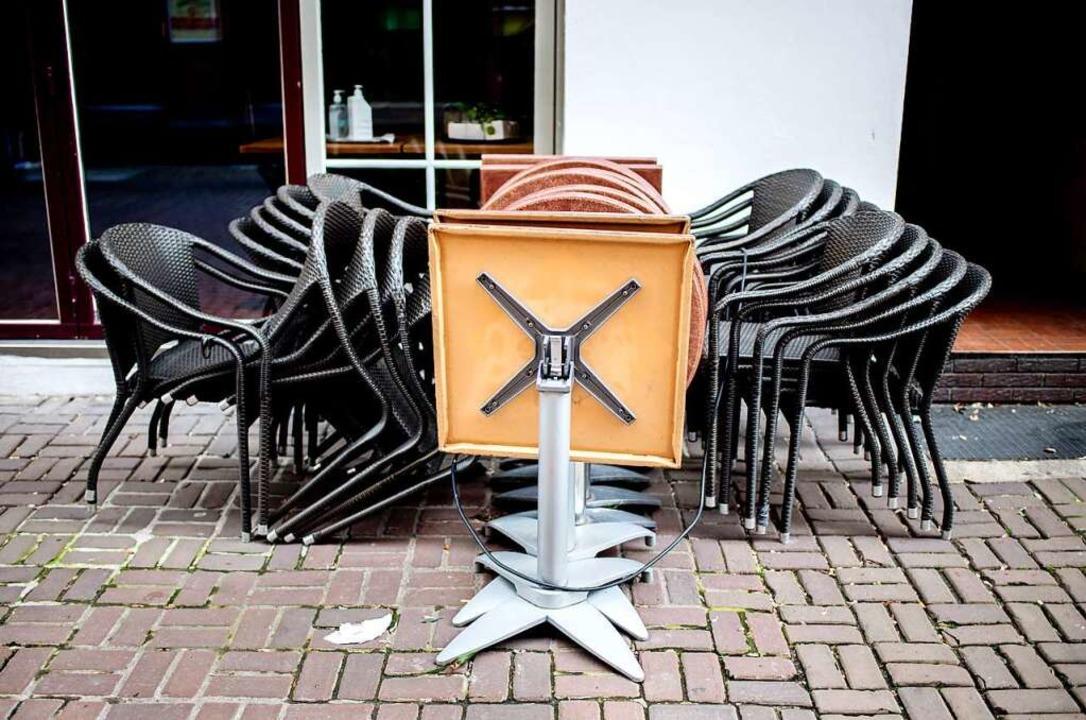 Corona-Lockdown: Stühle und Tische stehen vor einem geschlossenen Restaurant.  | Foto: Hauke-Christian Dittrich (dpa)