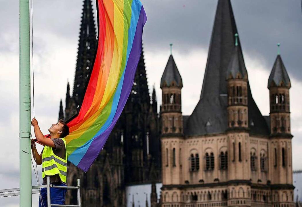 Mit dem Aufhängen der Regenbogenfahne ...schlechtlicher Beziehungen öffentlich.    Foto: Oliver Berg (dpa)