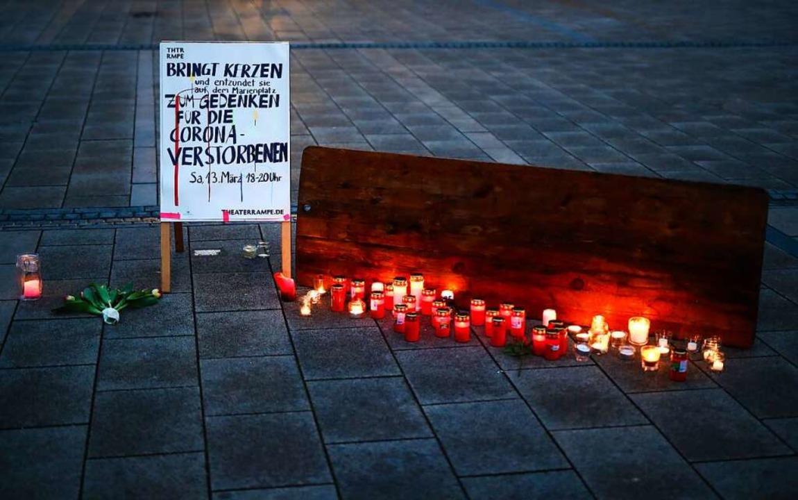 Die Kerzen brennen in Stuttgart für di...einer Corona-Infektion gestorben sind.  | Foto: Christoph Schmidt (dpa)