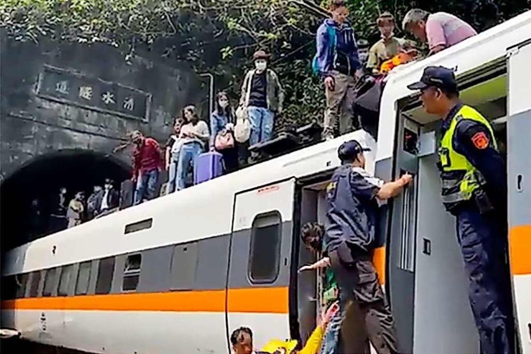 Passagieren wird geholfen, aus einem e...rchfahrt durch einen Tunnel entgleist.  | Foto: Uncredited/hsnews.com.tw/AP/dpa