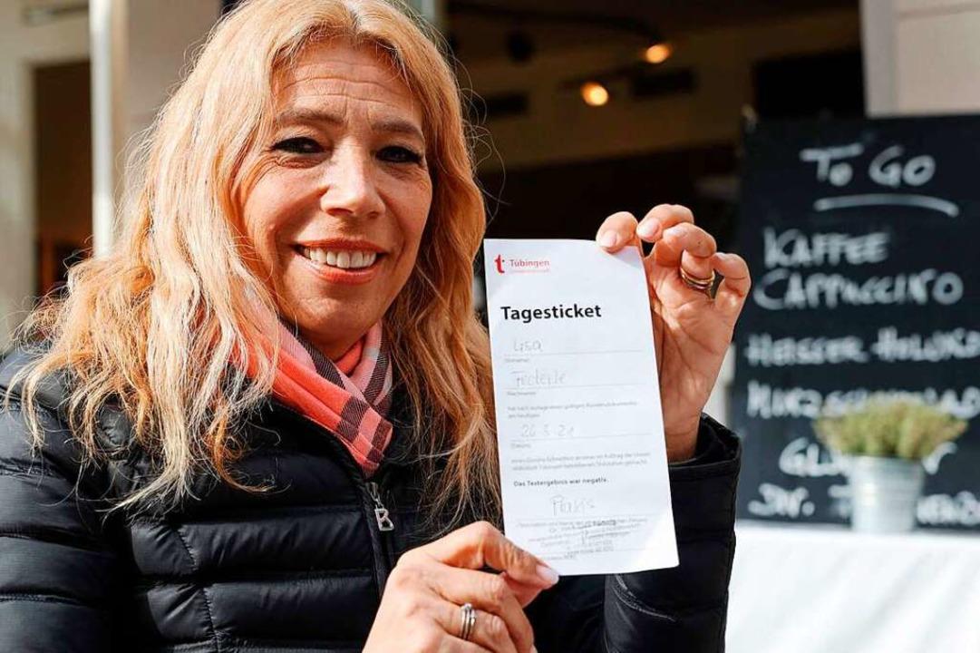 Lisa Federle zeigt ein Tagesticket, mi...el die Außengastronomie nutzen dürfen.    Foto: YANN SCHREIBER (AFP)