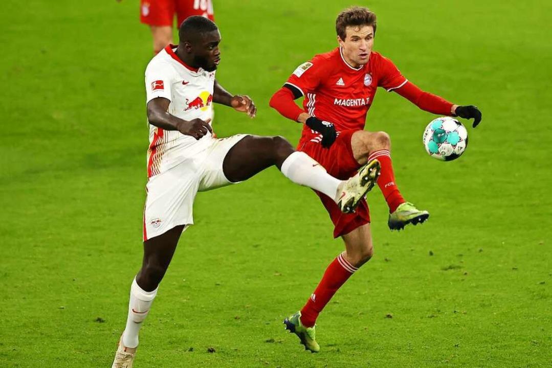 Dayot Upamecano (l) von RB Leipzig ver...an den Ball zu kommen.    (Archivbild)  | Foto: Alexander Hassenstein (dpa)