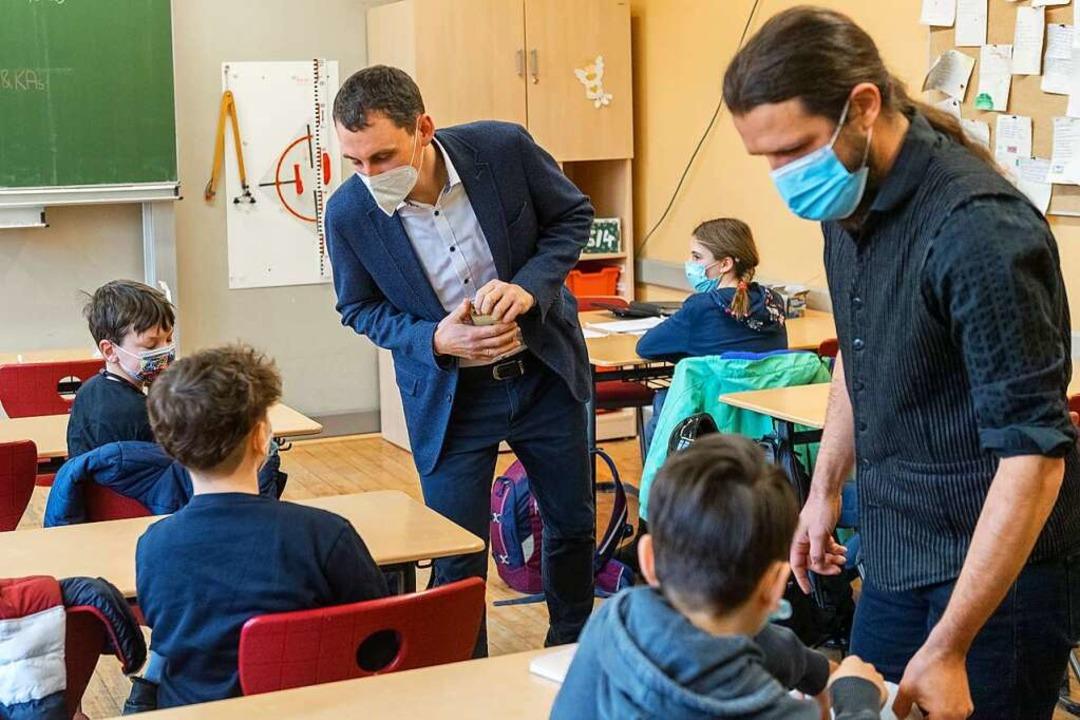 Lehrer überprüfen die Ergebnisse von Corona-Schnelltests im Klassenzimmer.  | Foto: Holger John (dpa)