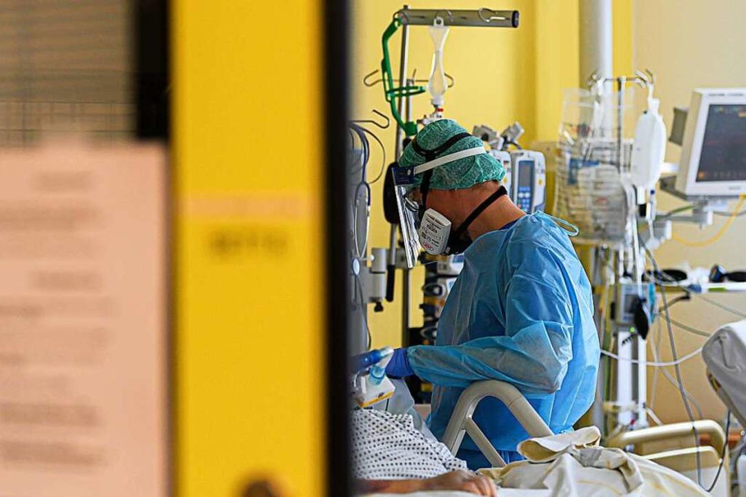 Ein Intensivpfleger ist auf der Covid-...gung von Corona-Patienten beschäftigt.    Foto: Robert Michael (dpa)