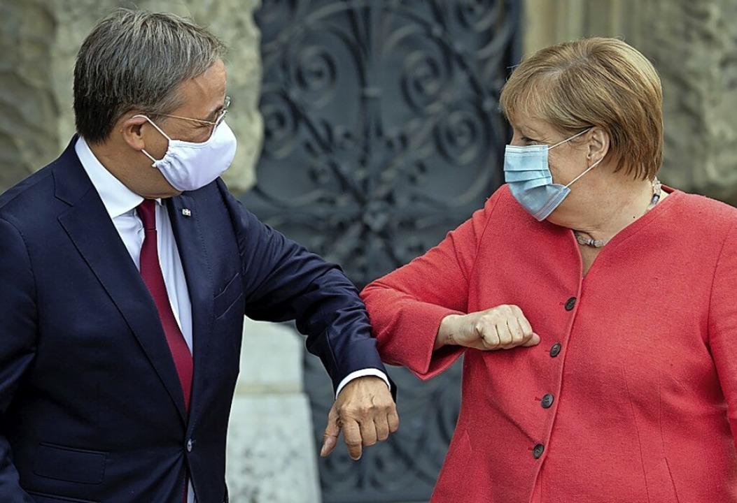 Laschet und  Merkel stimmen sich ab.  | Foto: FEDERICO GAMBARINI (AFP)